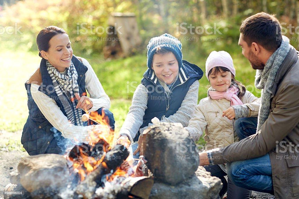 happy family roasting marshmallow over campfire stock photo