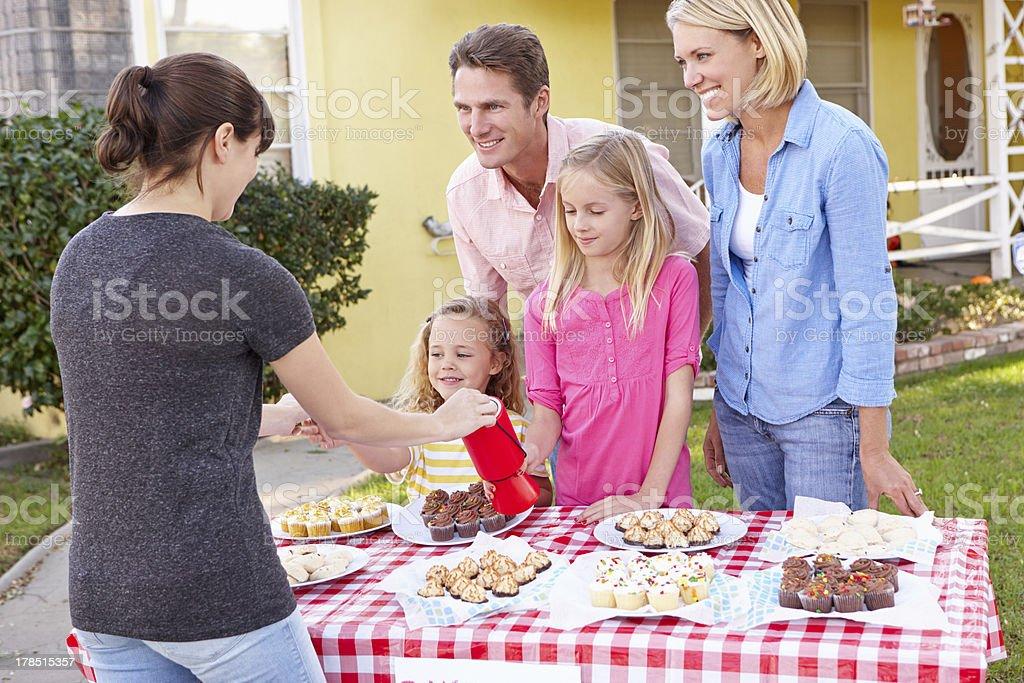 Happy family running charity bake sale stock photo