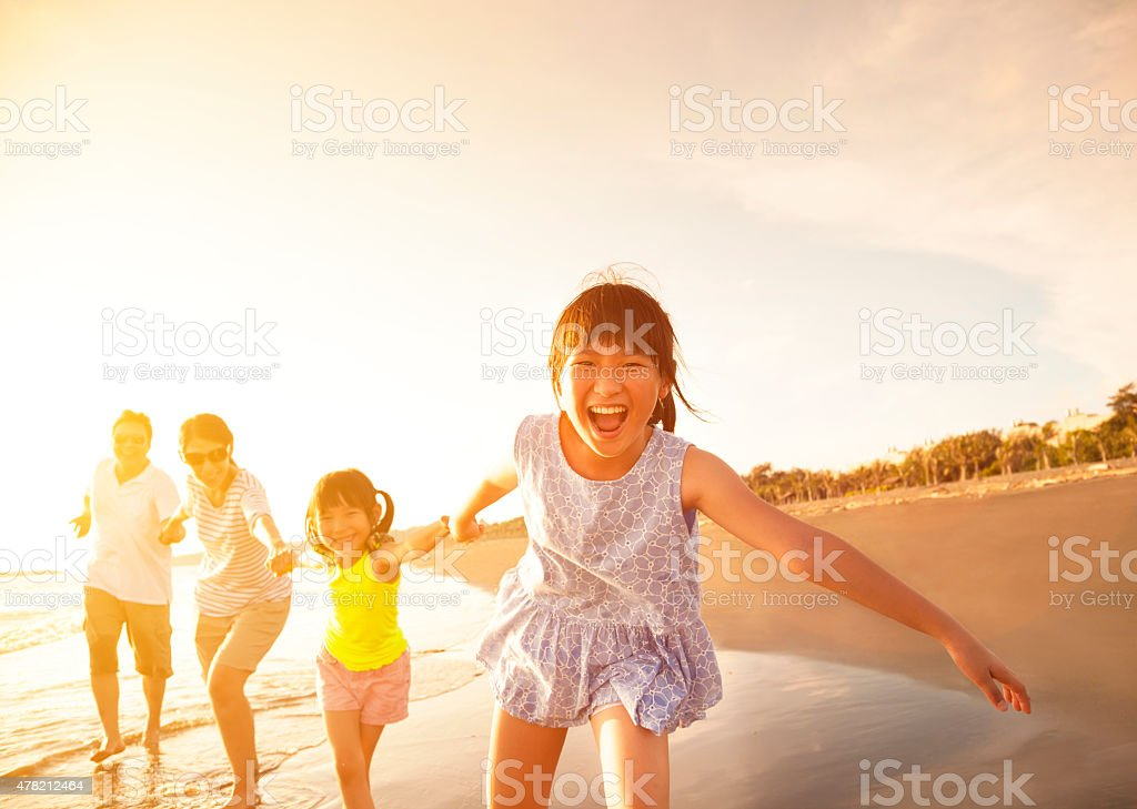 happy family running on the beach stock photo