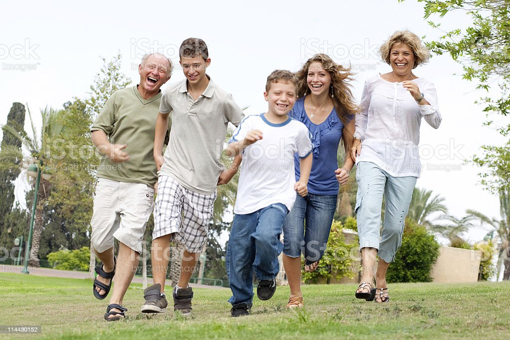 Happy family running outdoors and enjoying themselves royalty-free stock photo
