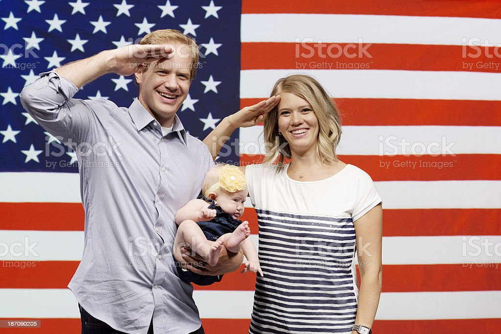 Happy family saluting in front of American flag royalty-free stock photo