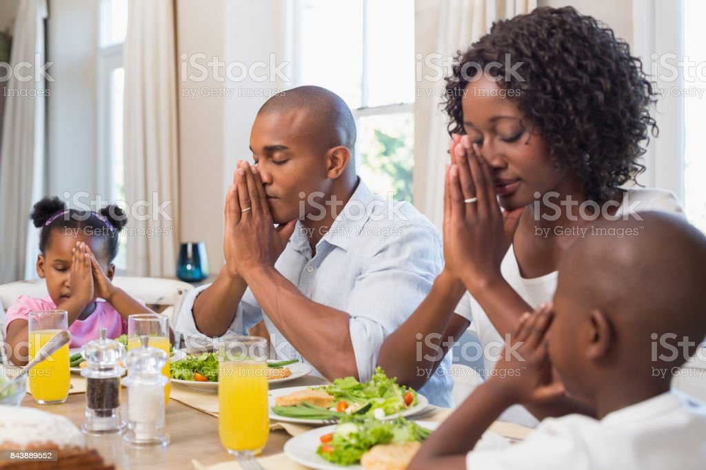 Happy family saying grace before meal stock photo