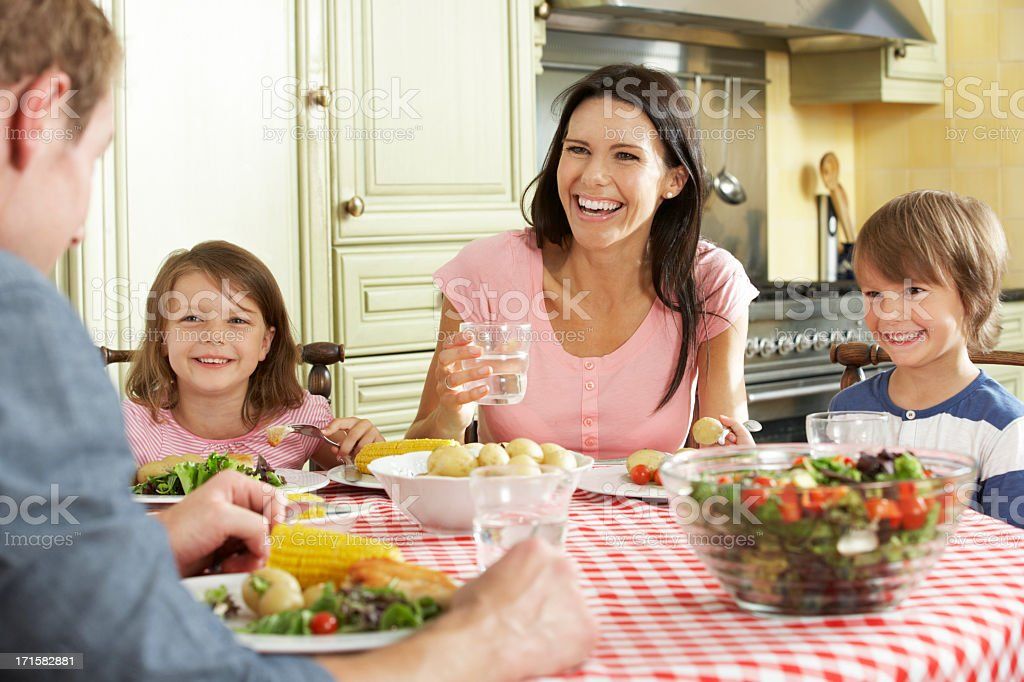 A happy family sharing a meal in the kitchen stock photo