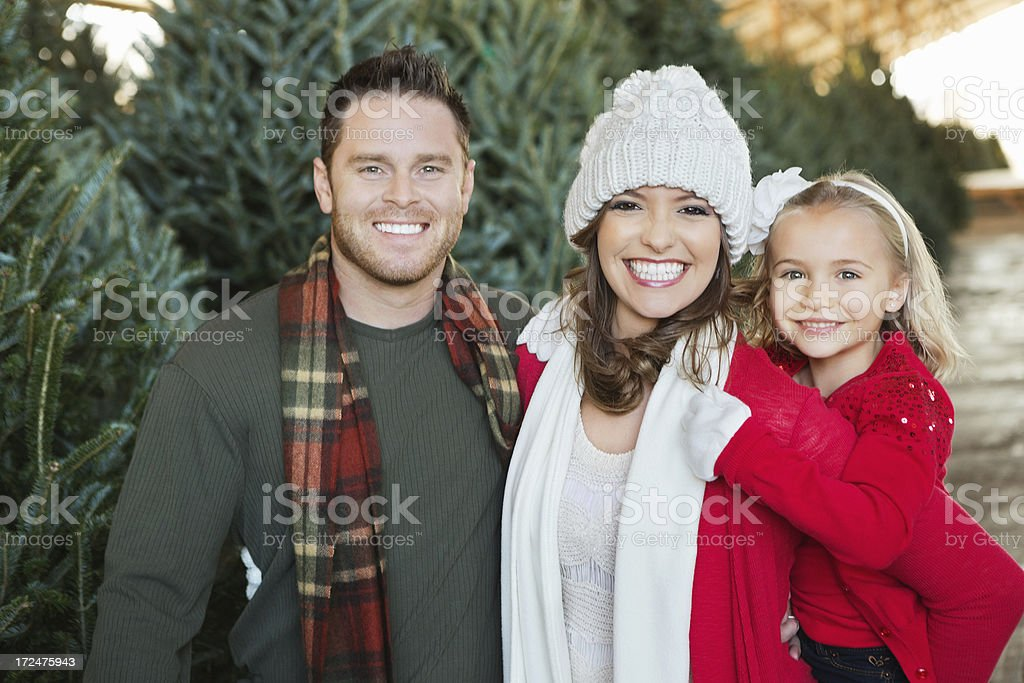 Happy family shopping for Christmas tree together stock photo
