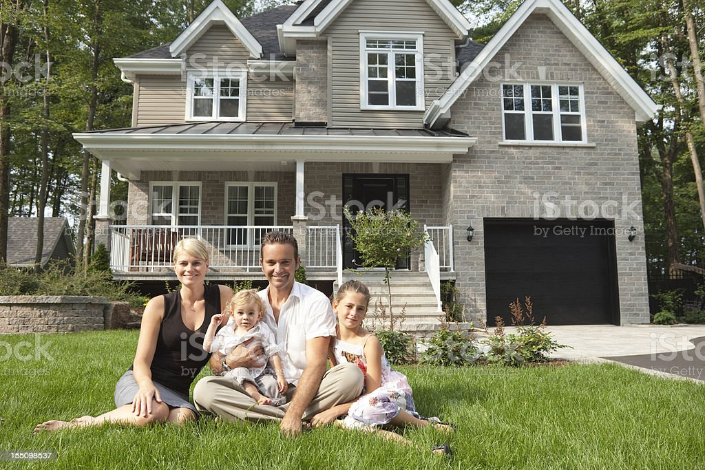 Happy Family Sitting In Front Of Their New House stock photo