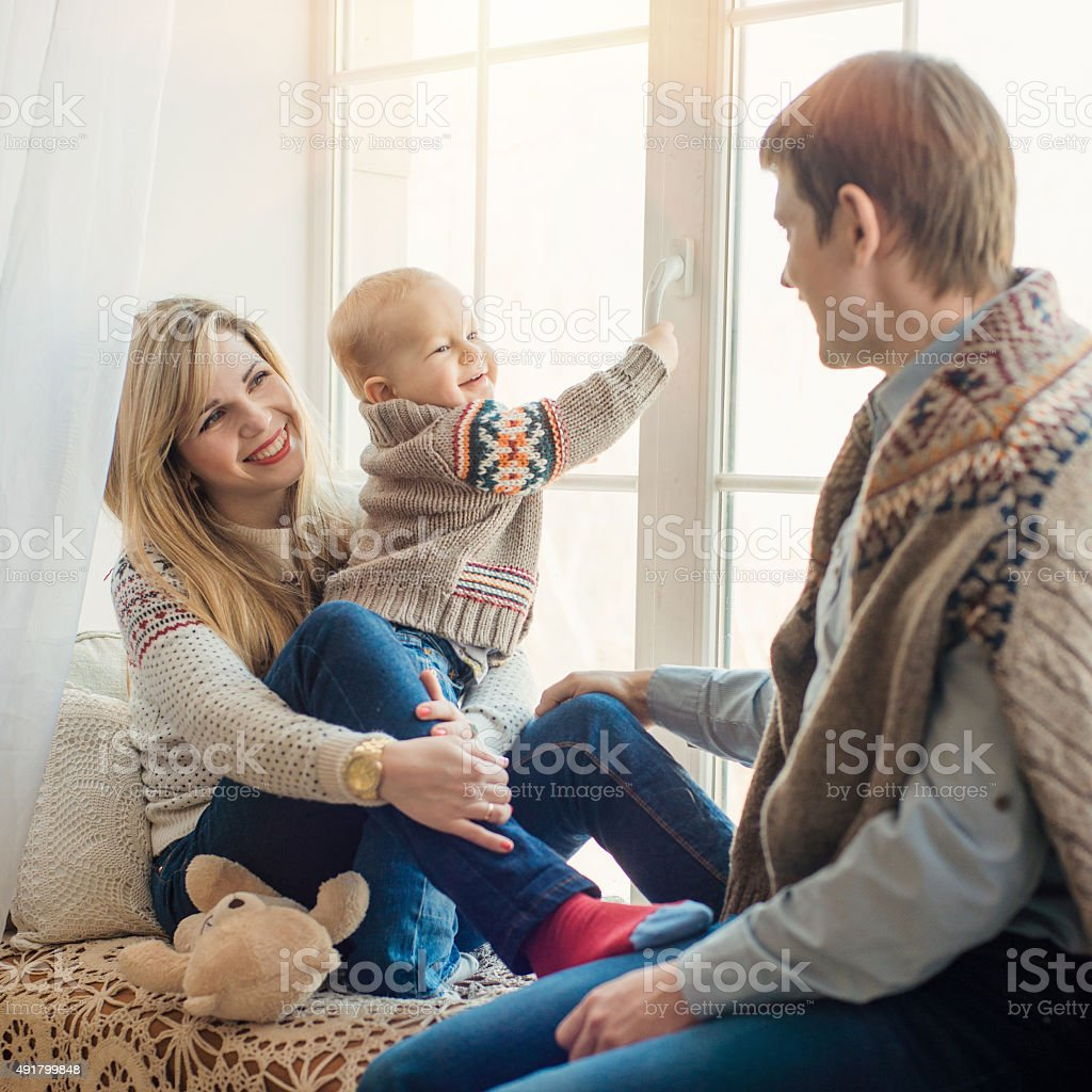 Happy family sitting in front of window in winter. stock photo