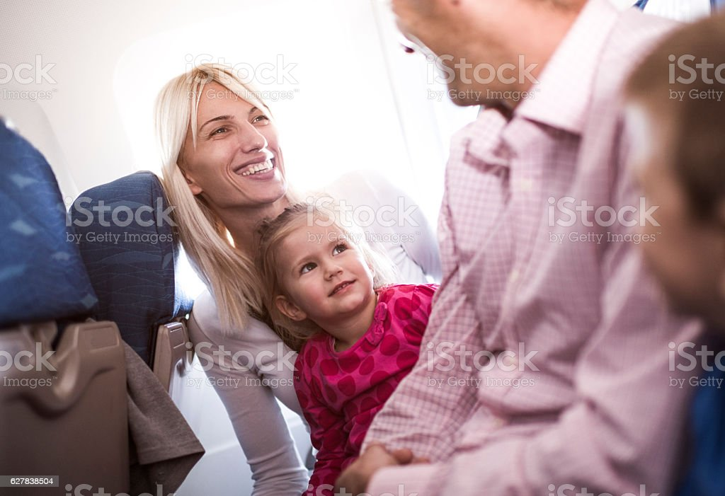Happy family sitting in the airplane and communicating. stock photo