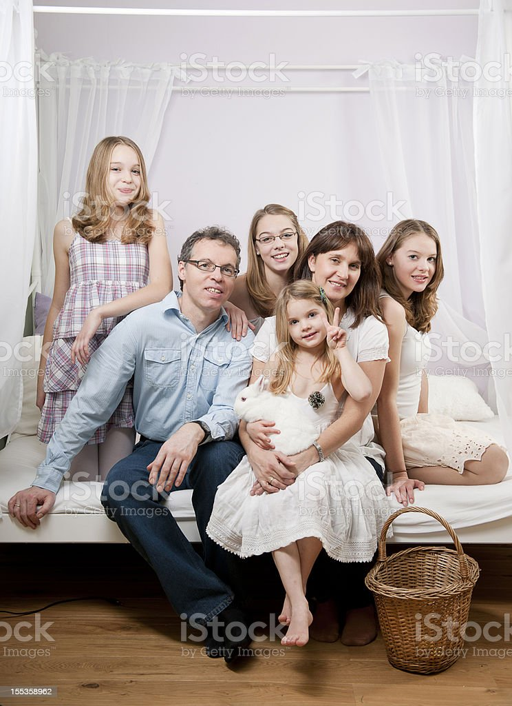 Happy family sitting on bed stock photo