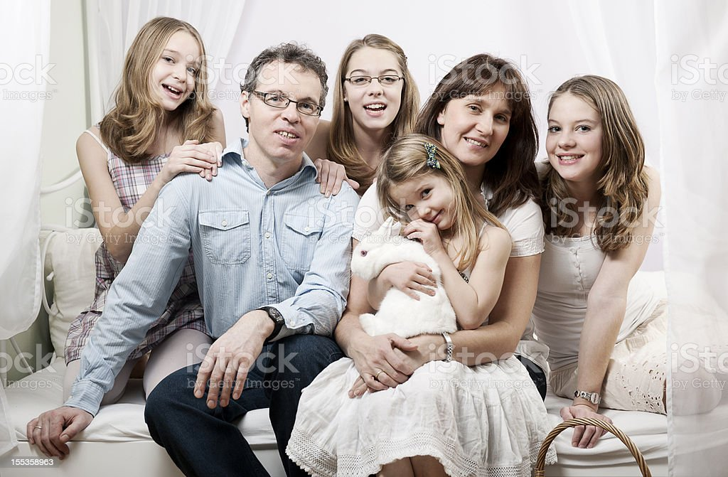 Happy family sitting on bed royalty-free stock photo
