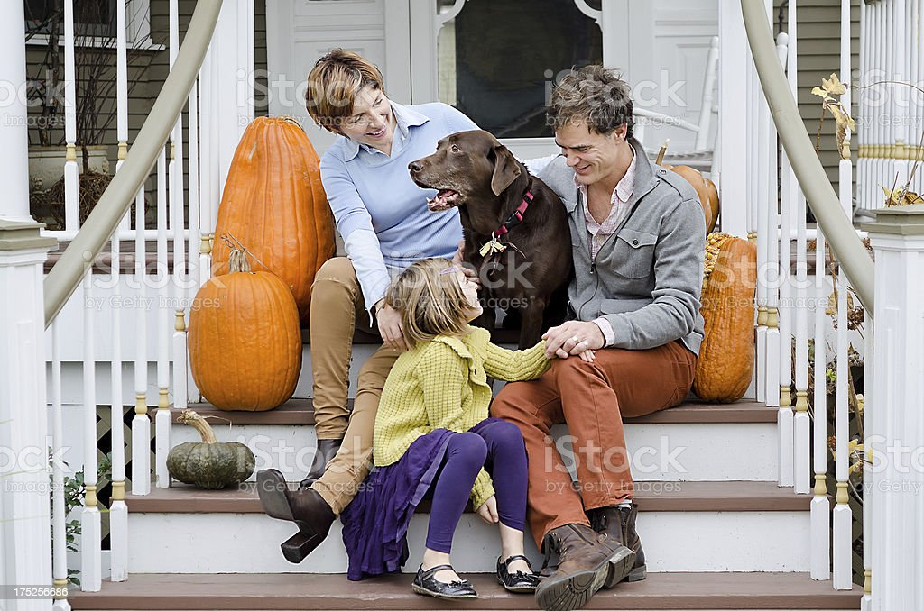 Happy Family Sitting on Porch Stairs with Labrador Retriever Dog stock photo