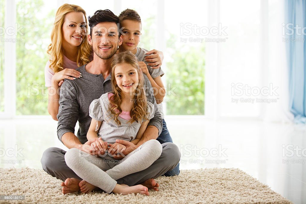 Happy family sitting on the floor at home stock photo