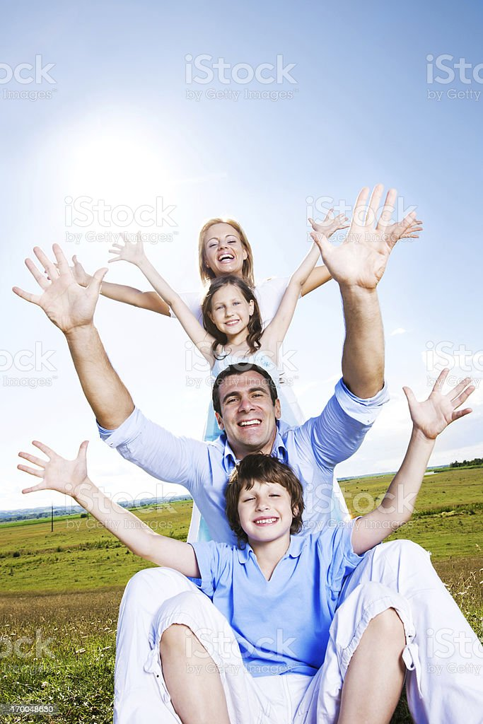 Happy family sitting outdoors against the blue sky. royalty-free stock photo