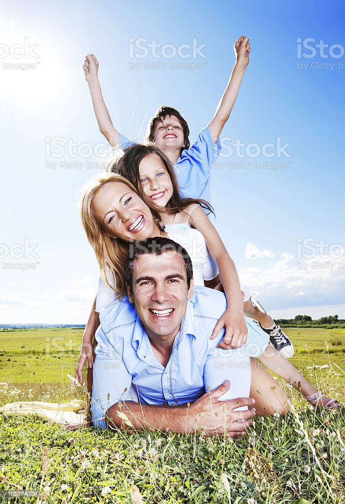 Happy family sitting outdoors against the blue sky royalty-free stock photo