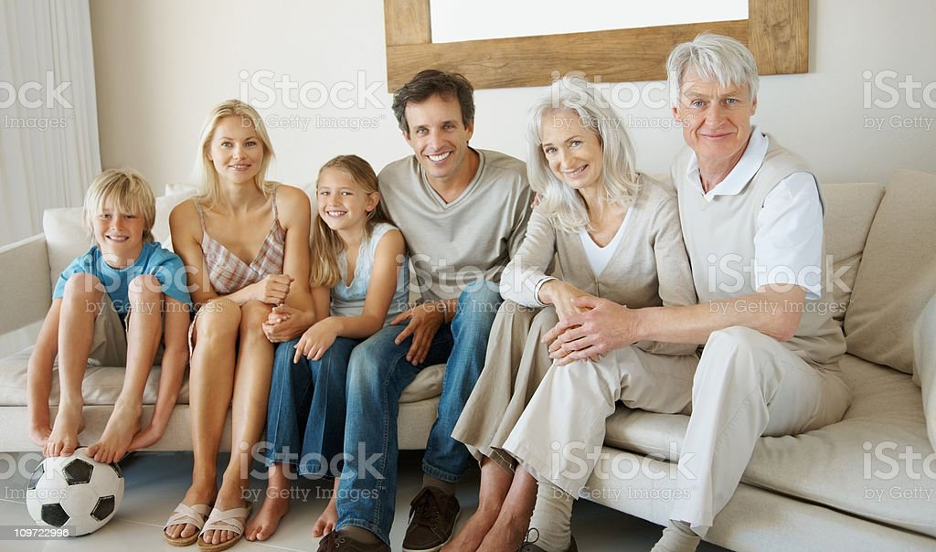 Happy family sitting together on couch at home royalty-free stock photo