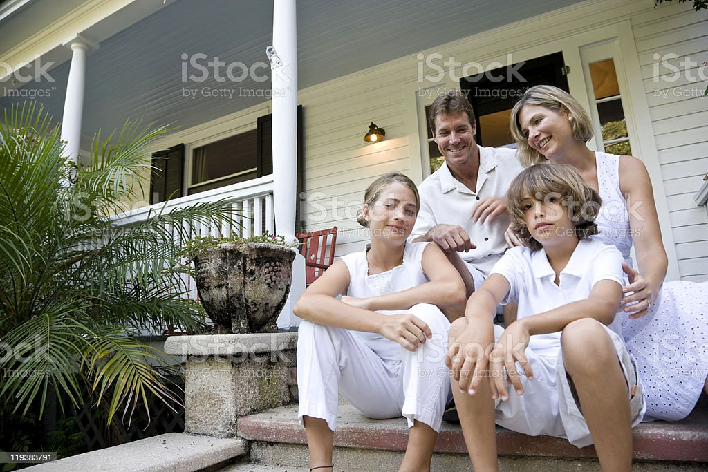 Happy family sitting together on front porch steps stock photo