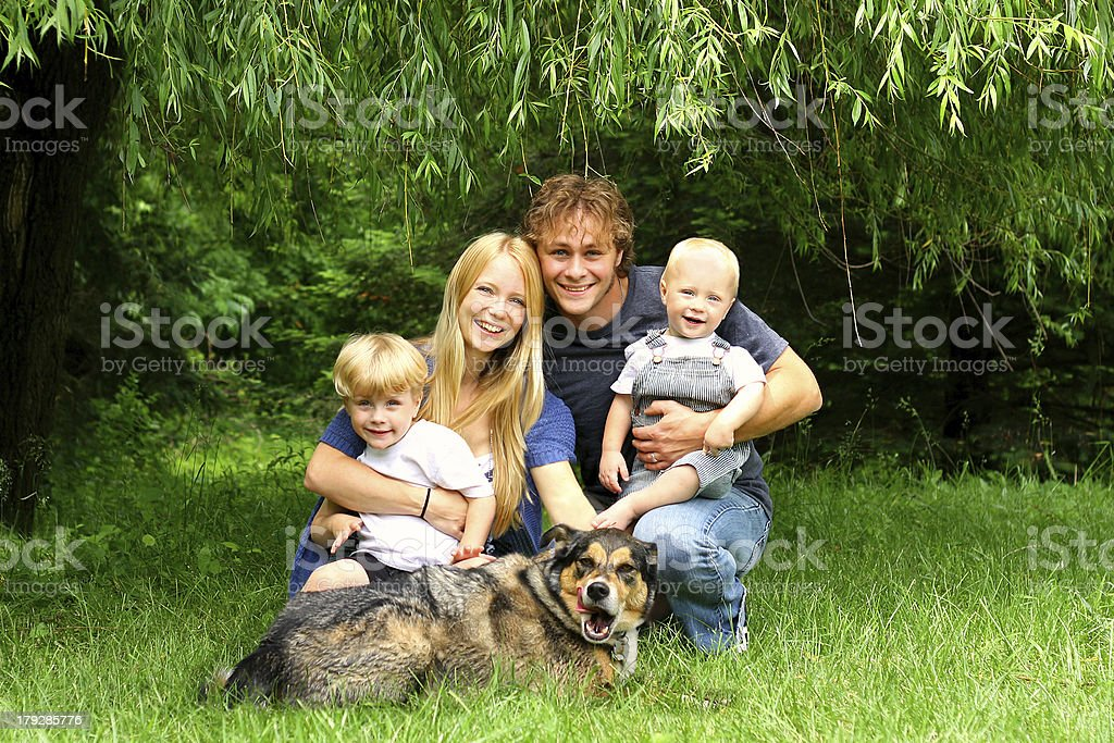 Happy Family Sitting Under Willow Tree royalty-free stock photo