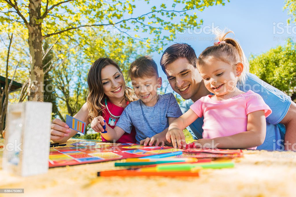 Happy family spending a day outdoors and playing board game. stock photo