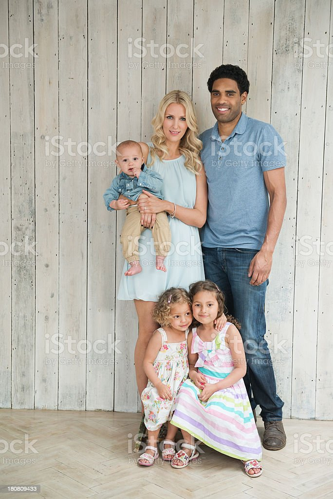 Happy Family Standing Against Wooden Wall royalty-free stock photo