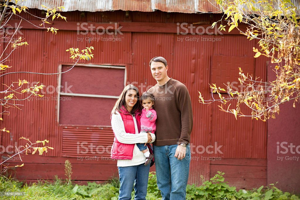Happy Family Standing in Front of Barn During Autumn royalty-free stock photo