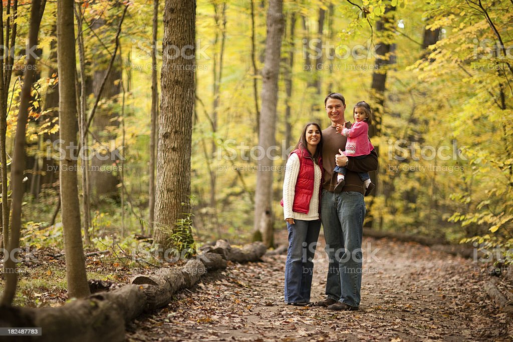 Happy Family Standing on Trail in Autumn Woods royalty-free stock photo
