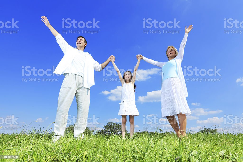 Happy family standing outdoor with raised hand up. royalty-free stock photo