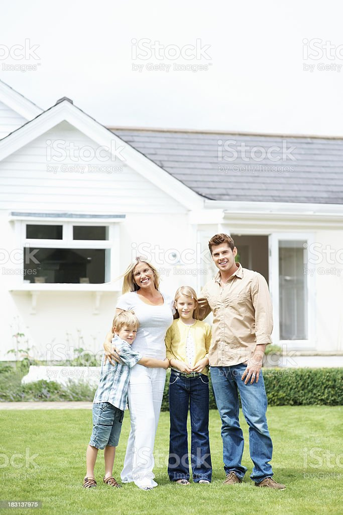 Happy family standing outside their house on a sunny day royalty-free stock photo
