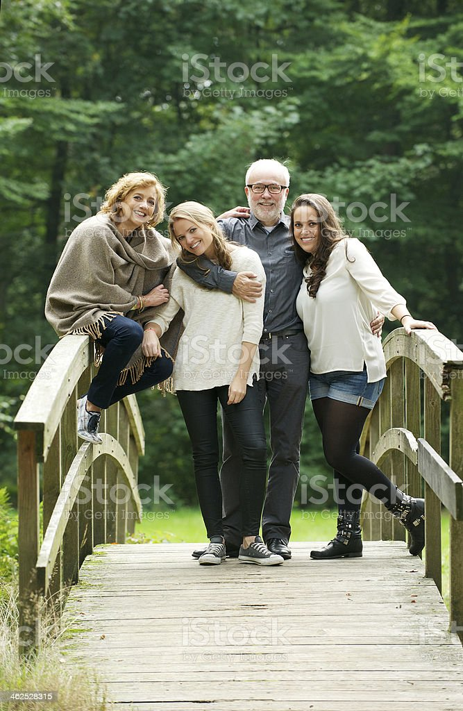 Happy family standing together on a bridge in the forest stock photo