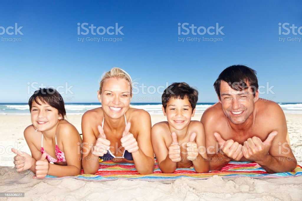 Happy family sunbathing while giving thumbs up royalty-free stock photo