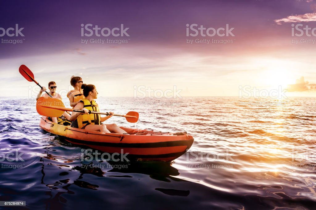 Happy family swims kayaking at sea sunset stock photo