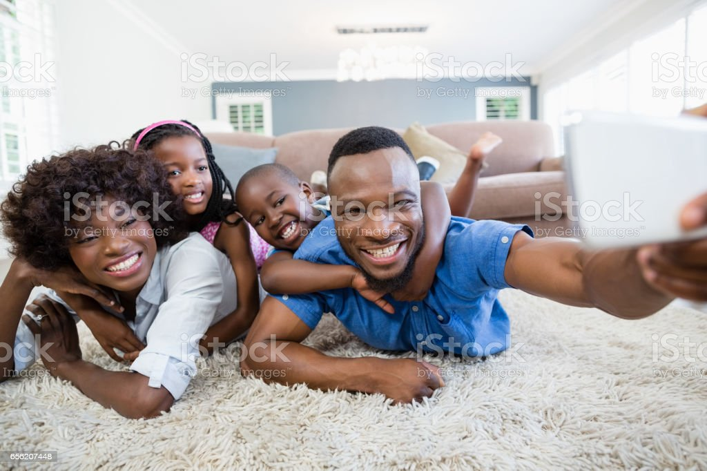 Happy family taking a selfie from mobile phone in living room stock photo
