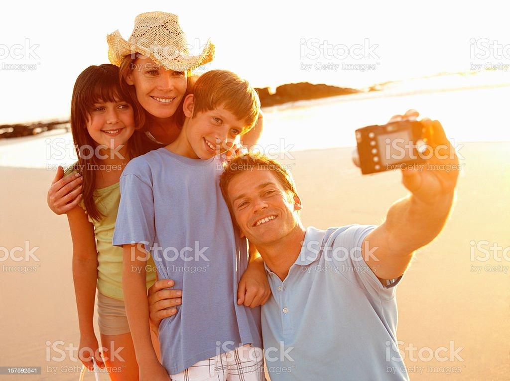 Happy family taking self portrait at beach royalty-free stock photo