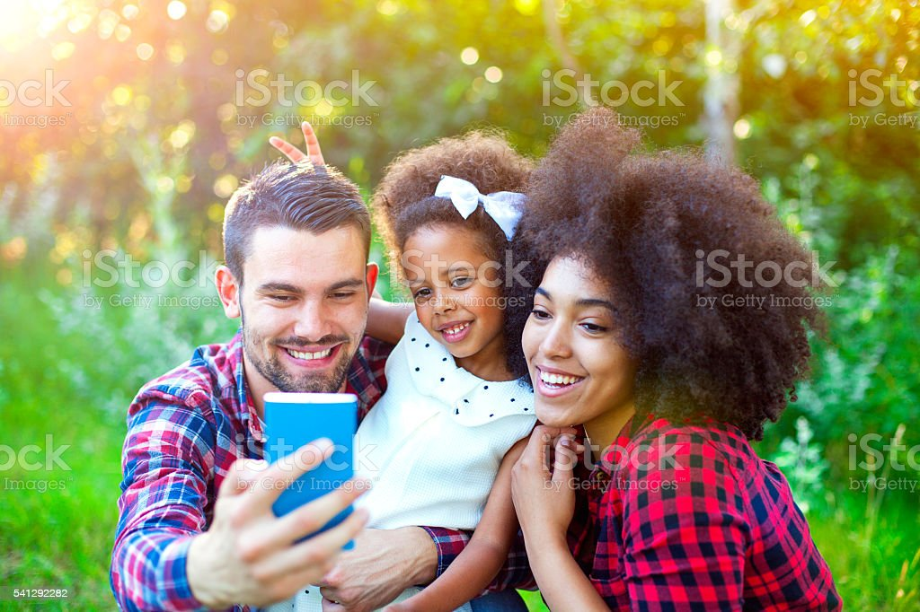 Happy family taking selfie by smartphone outdoors stock photo