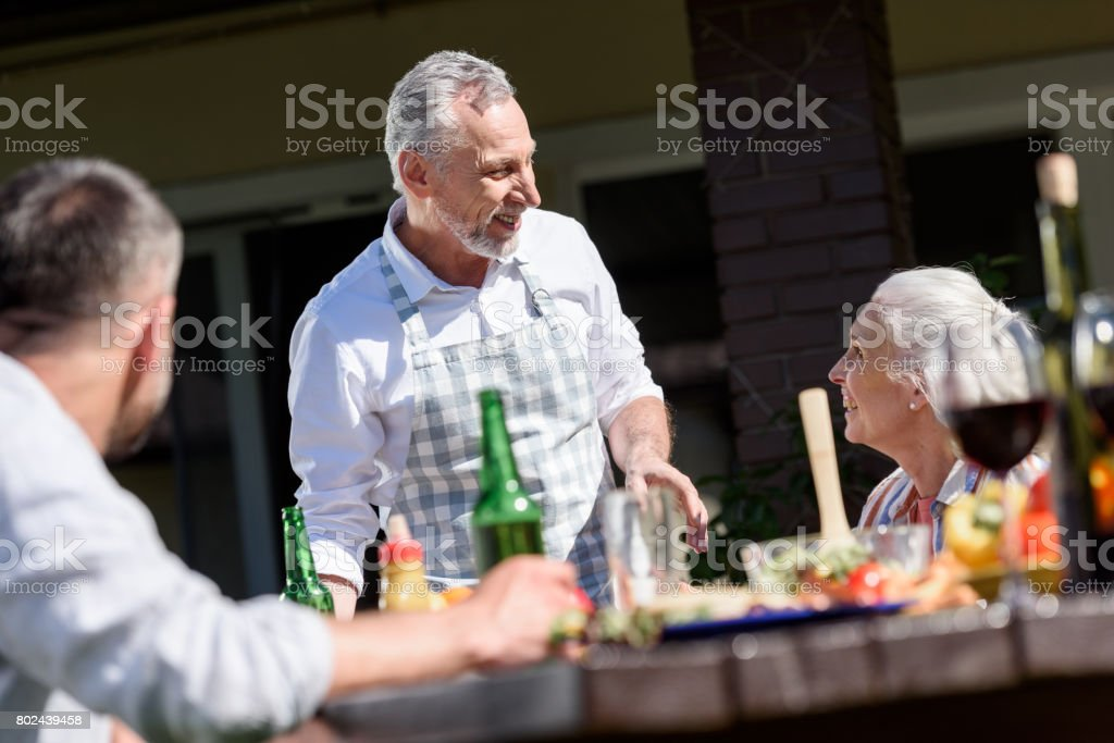happy family talking during lunch on patio at daytime stock photo