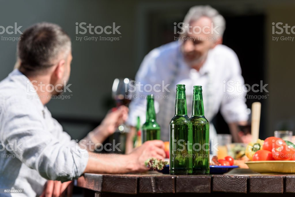happy family talking while having lunch on patio at daytime. Selective focus on bottles stock photo