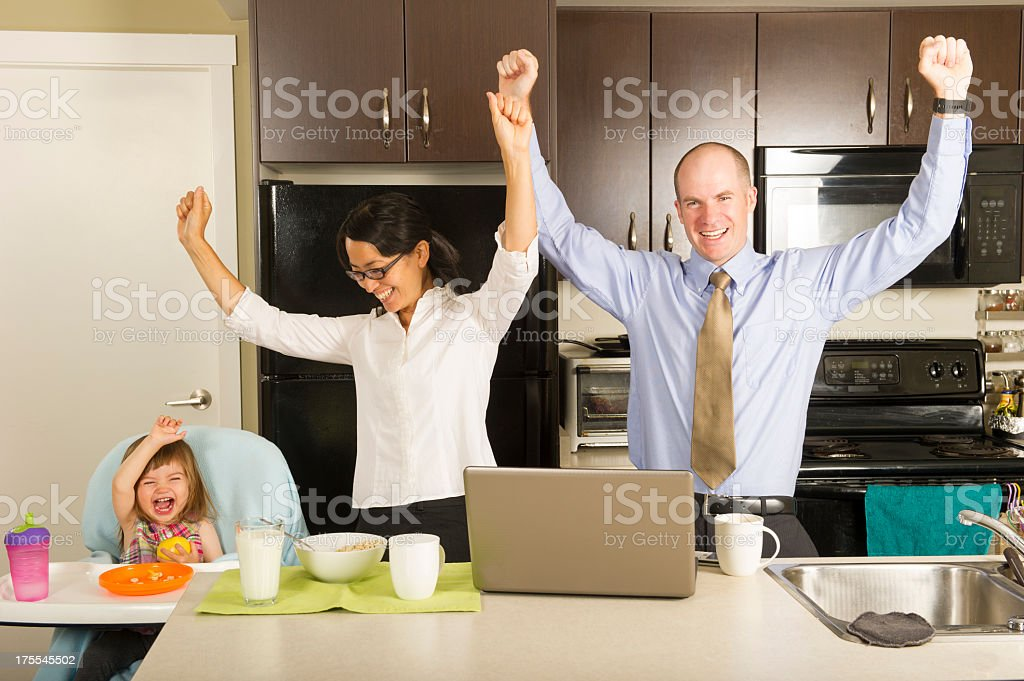 Happy family throwing hands in the air in a kitchen stock photo
