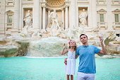 Happy family trowing coins at Trevi Fountain, Rome, Italy for
