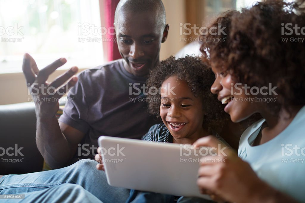 Happy family using tablet computer on sofa stock photo