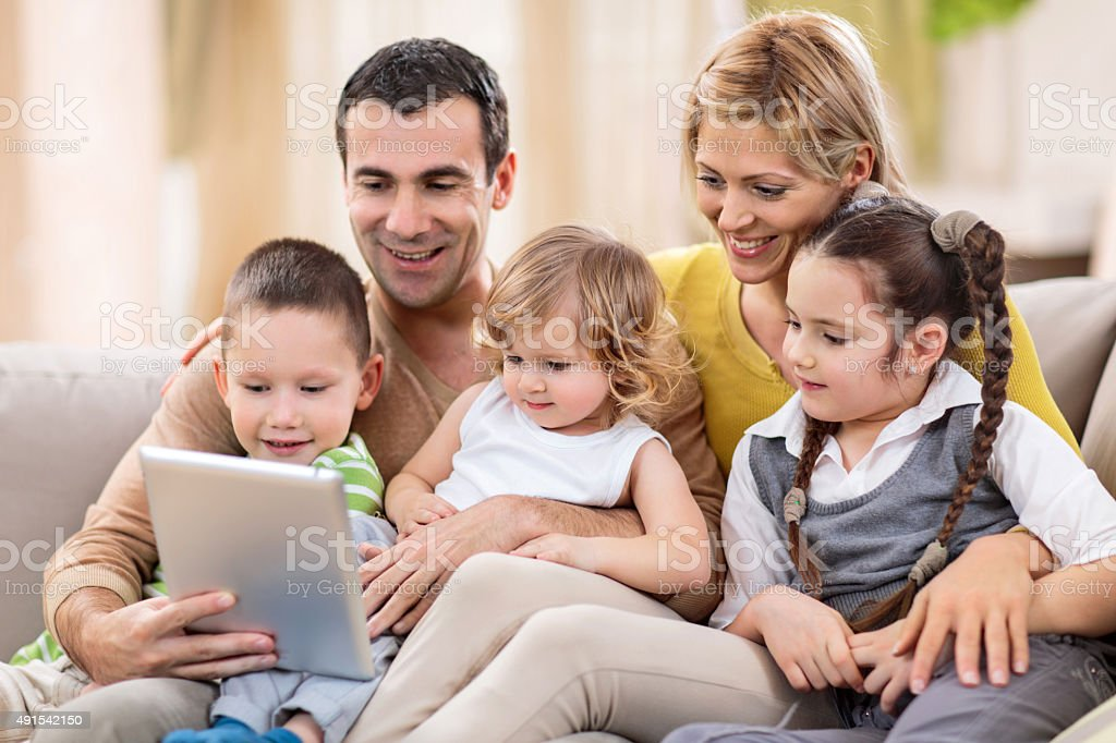 Happy family using touchpad at home. stock photo