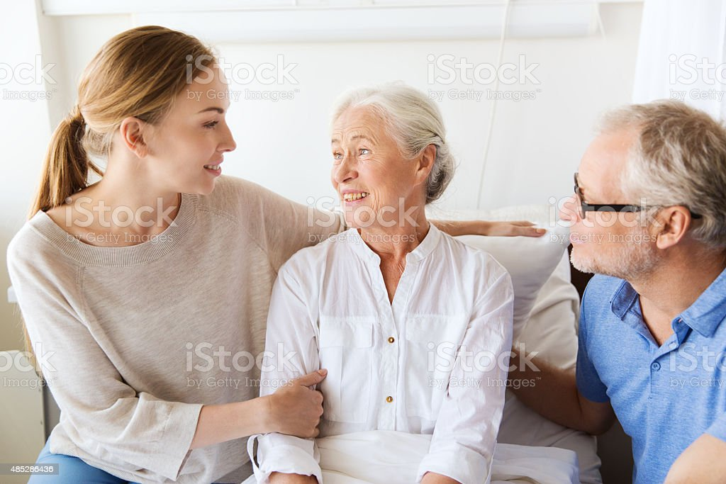 happy family visiting senior woman at hospital stock photo
