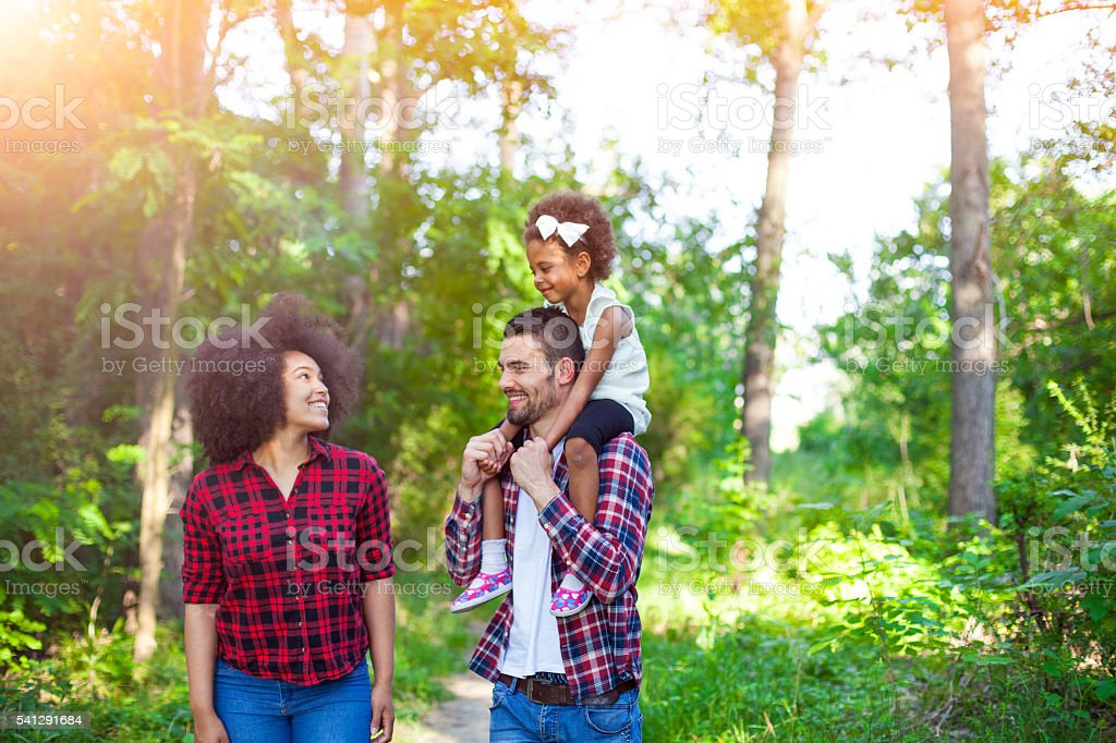 Happy family walking along a path in the woods stock photo