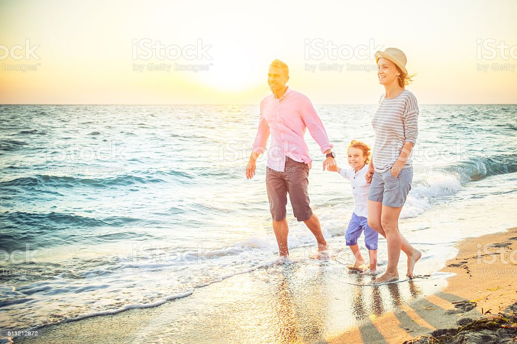 Happy family walking along a sandy beach stock photo