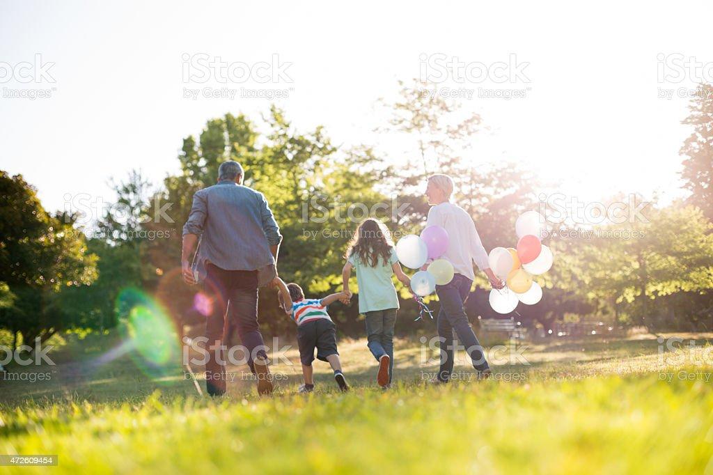 Happy family walking at the park stock photo