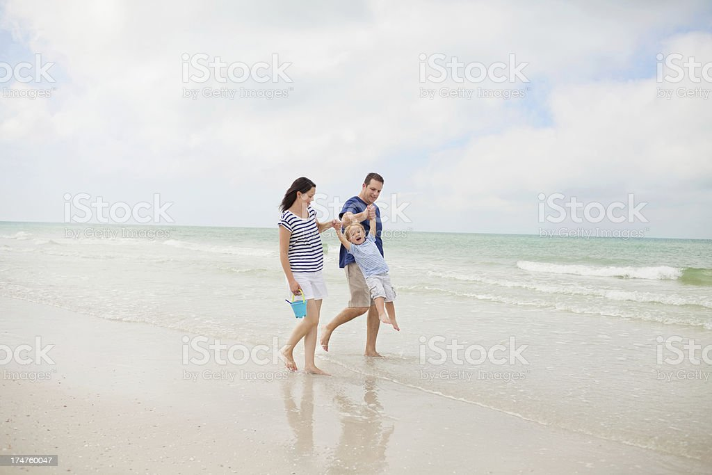 Happy Family Walking At Water's Edge On Beach royalty-free stock photo