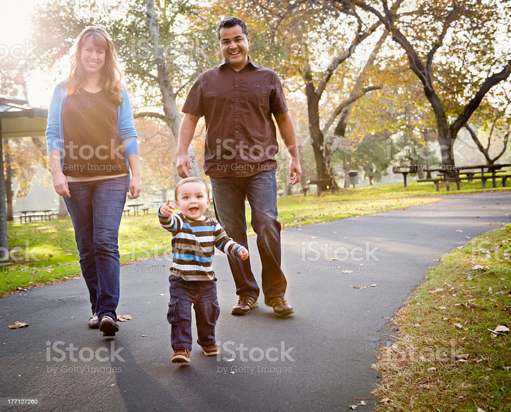 Happy family walking down the park street stock photo