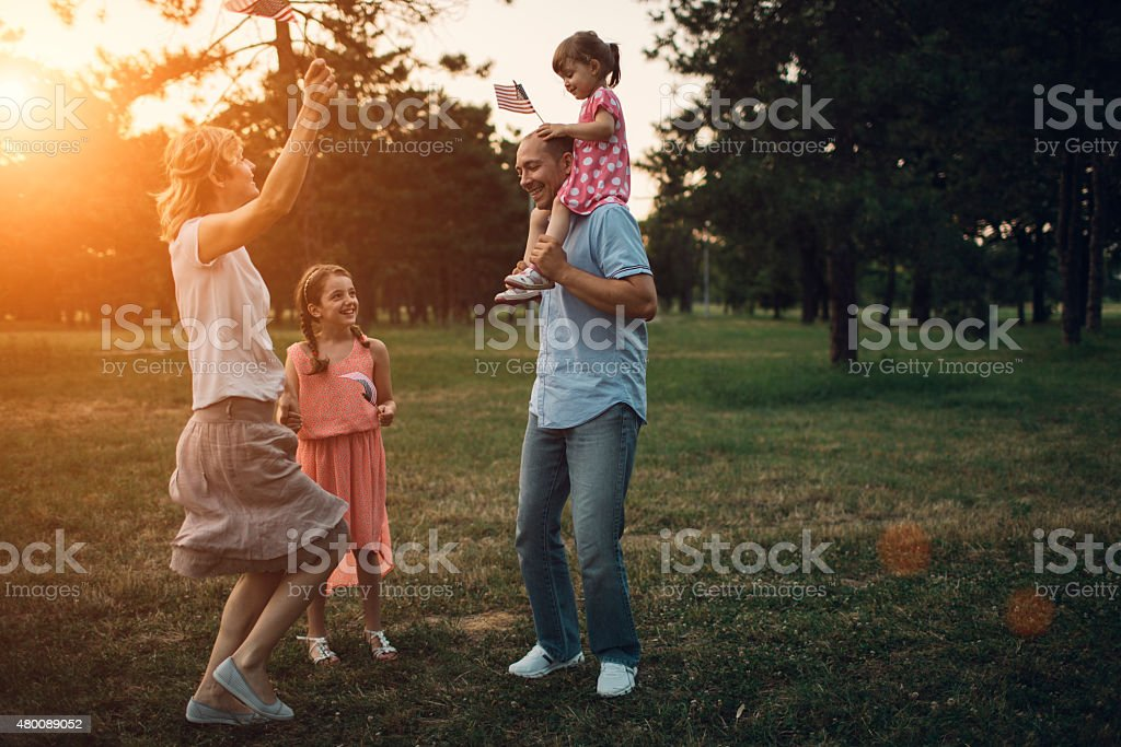 Happy Family Walking In A Park. stock photo