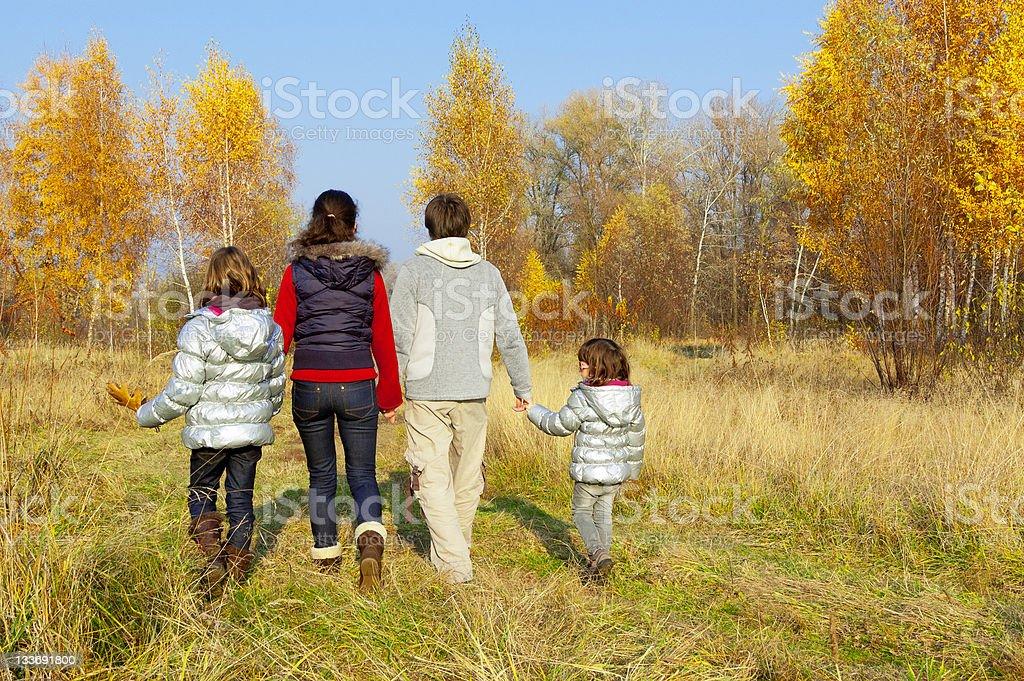 Happy family walking in autumn park royalty-free stock photo