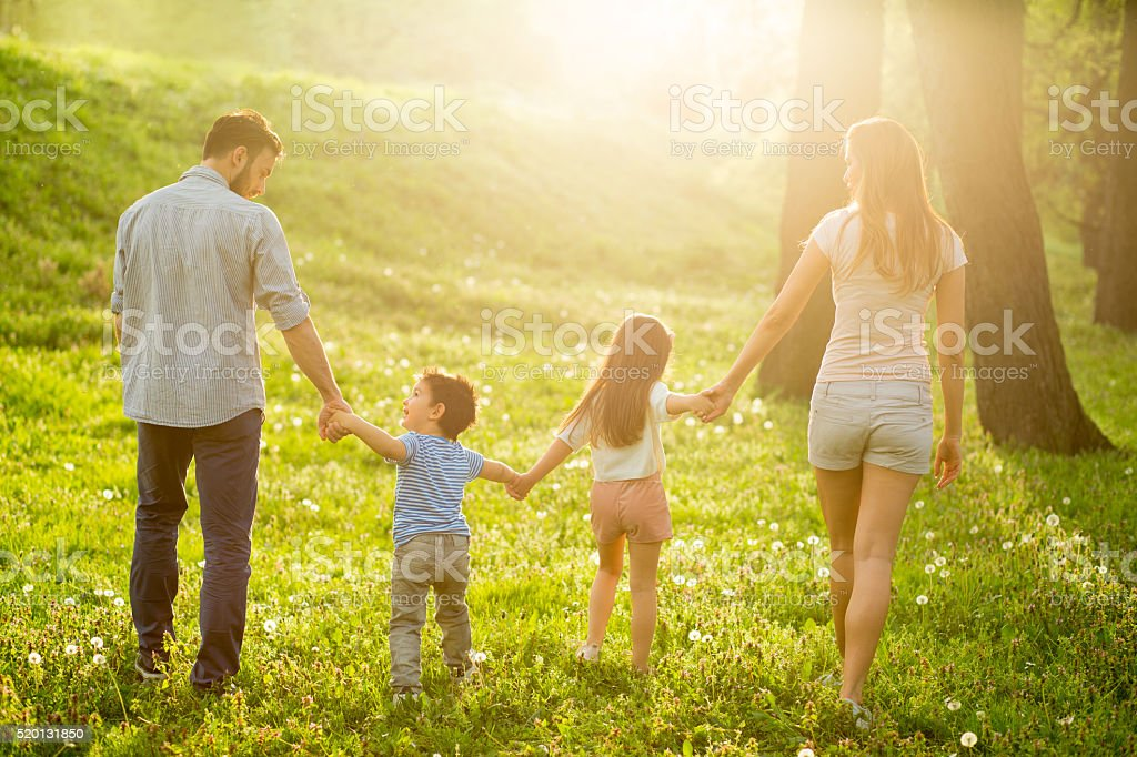 Happy family walking in the park on summer day stock photo
