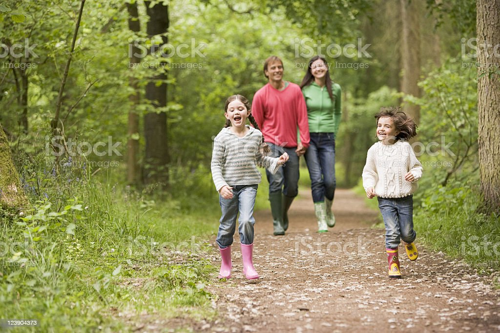 Happy family walking on a path in the woods stock photo