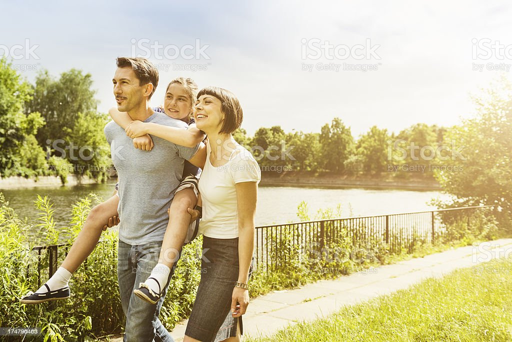 Happy family walking outdoors in the park royalty-free stock photo