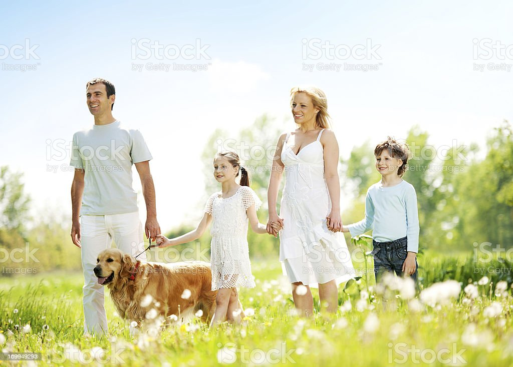 Happy family walking their dog in a park. royalty-free stock photo